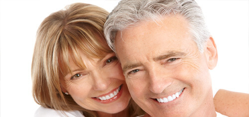 Close-up picture of a smiling couple looking directly into the camera showing their happiness with  having holistic dental work done in Costa Rica.  The woman has medium brown hair and the man has white hair.
