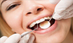Picture of a smiling woman in a dentist chair having a teeth cleaning procedures by Premier Holistic Dental in London.